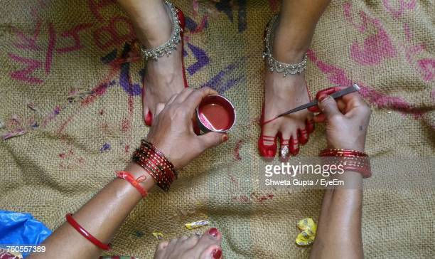 High Angle View Of Woman Applying Henna On Foot