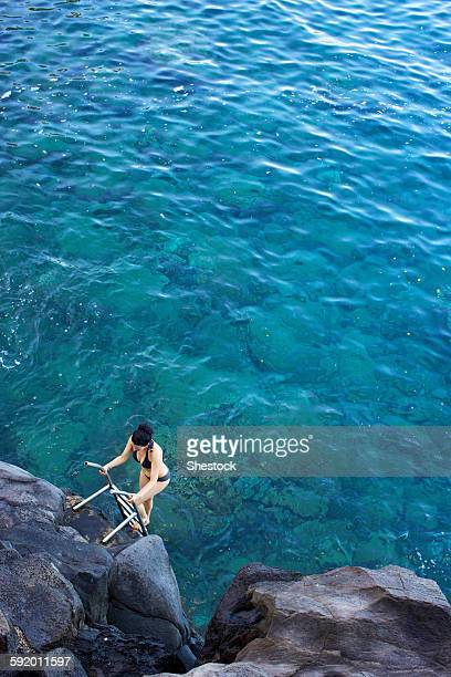 High angle view of woman climbing ladder out of ocean