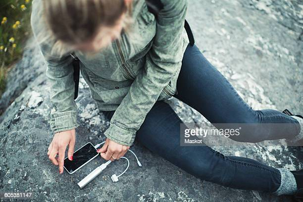 High angle view of woman connecting portable charger to smart phone on rock