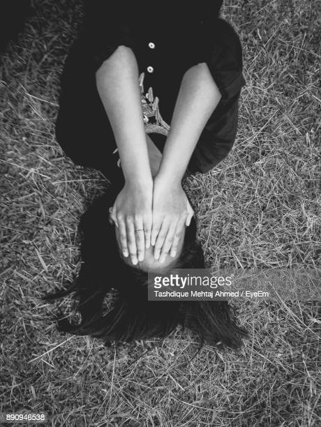 High Angle View Of Woman Covering Face With Hands While Lying Down On Grass