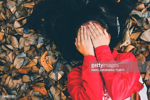 High Angle View Of Woman Covering Face With Hands While Relaxing On Field During Autumn