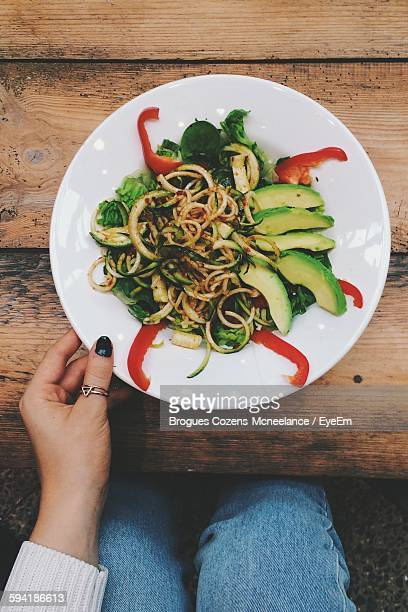 High Angle View Of Woman Eating Noodles At Table