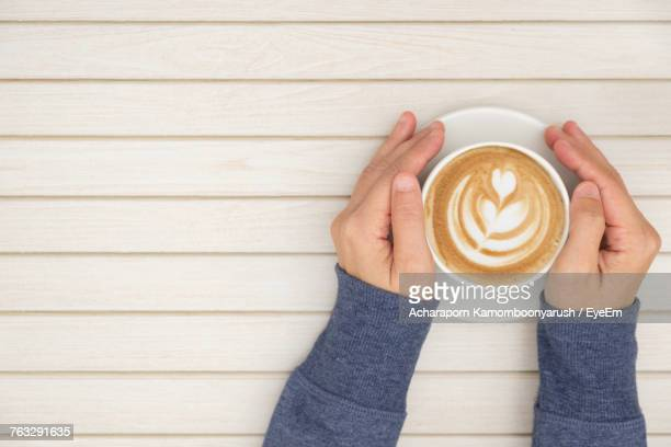 High Angle View Of Woman Holding Coffee Cup On Table