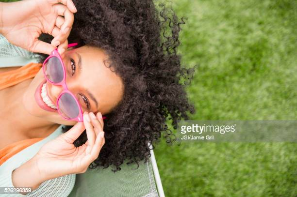 High angle view of woman holding sunglasses in chair outdoors