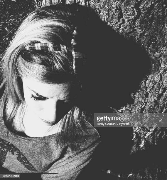 High Angle View Of Woman Leaning On Tree Trunk