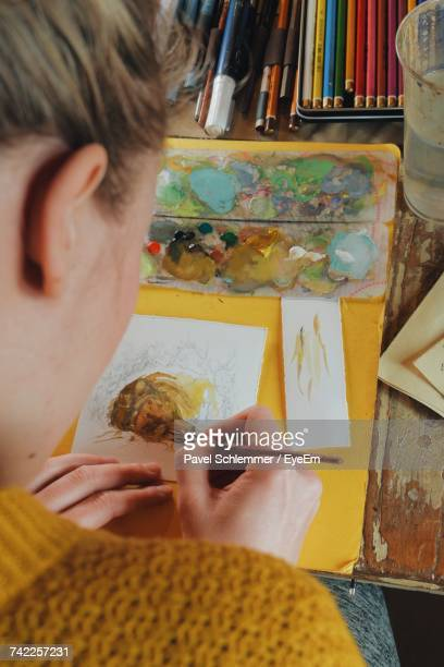 High Angle View Of Woman Painting On Paper