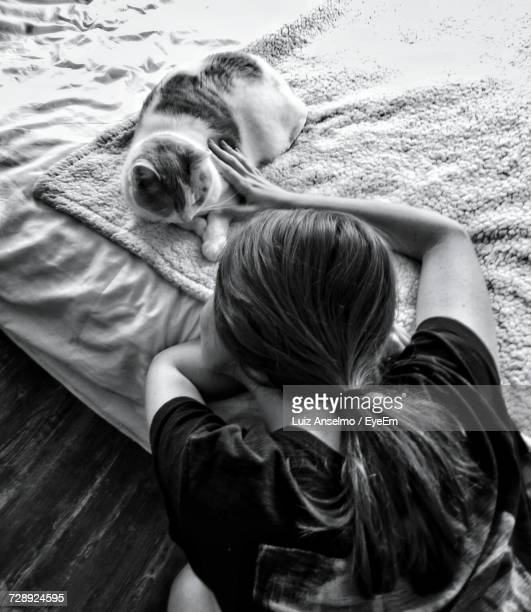 High Angle View Of Woman Petting Cat Lying On Bed At Home