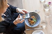 High angle view of woman photographing food through mobile phone in restaurant