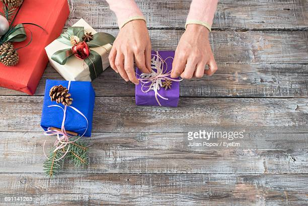 High Angle View Of Woman Preparing Christmas Gifts On Wooden Table