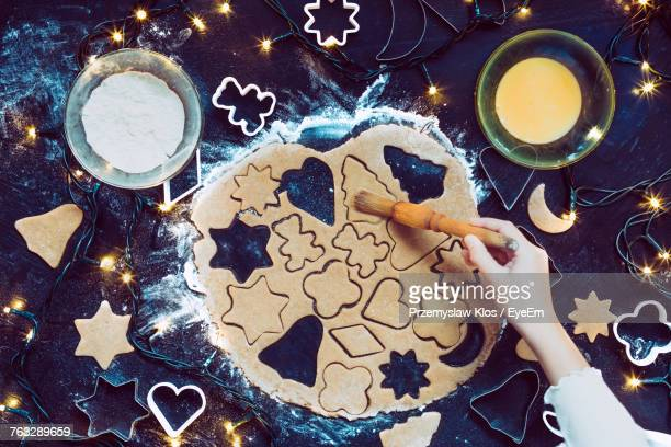 High Angle View Of Woman Preparing Cookies On Table