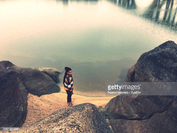 High Angle View Of Woman Standing By Rock On Shore At Beach