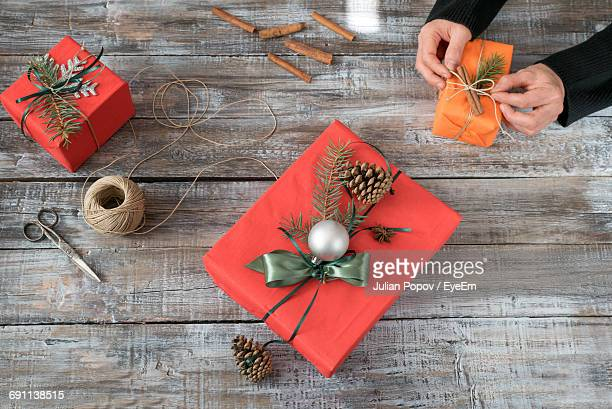High Angle View Of Woman Tying Gift During Christmas On Table