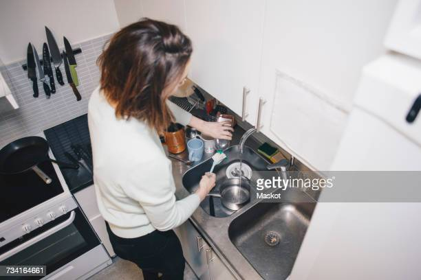 High angle view of woman washing dishes in kitchen sink at dorm
