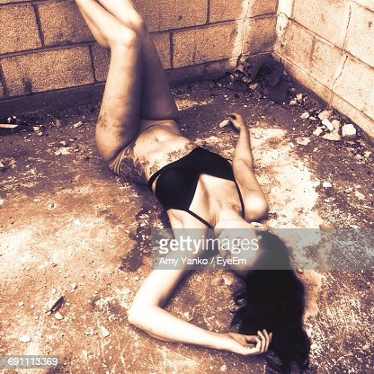 High Angle View Of Woman Wearing Lingerie Lying In Abandoned Building
