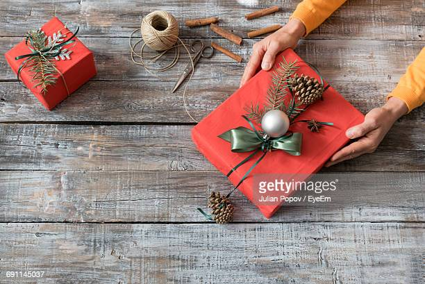 High Angle View Of Woman With Gift During Christmas On Table