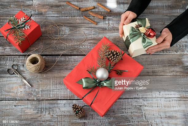 High Angle View Of Woman With Gifts During Christmas On Table
