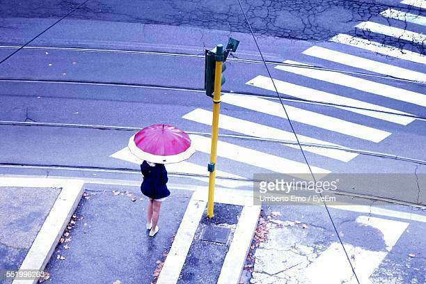 High Angle View Of Woman With Umbrella Waiting At Roadside