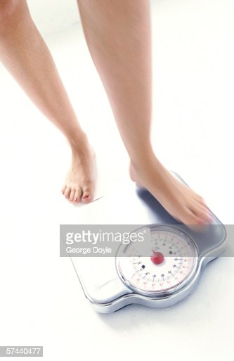 high angle view of woman's feet on a weighing scale : Stock Photo