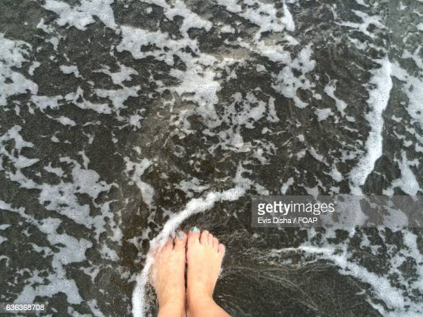 High angle view of woman's foot on water