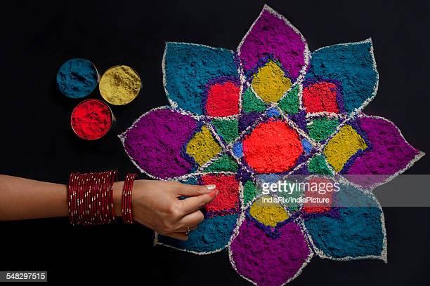 High angle view of womans hand making rangoli