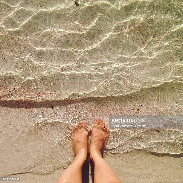 High Angle View Of Women Foot On Water