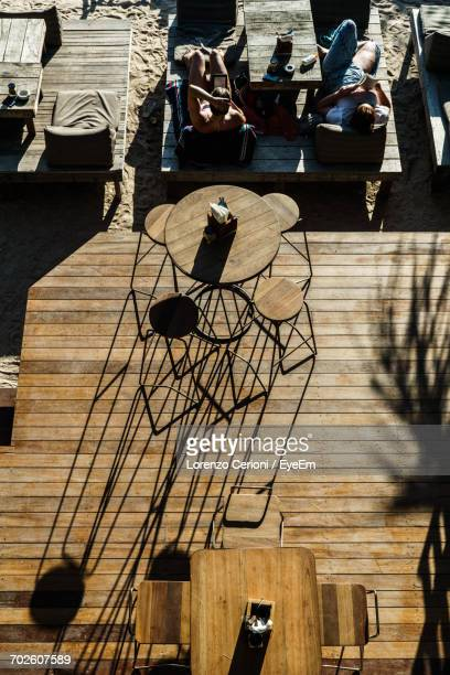 High Angle View Of women Relaxing By Patio At Beach