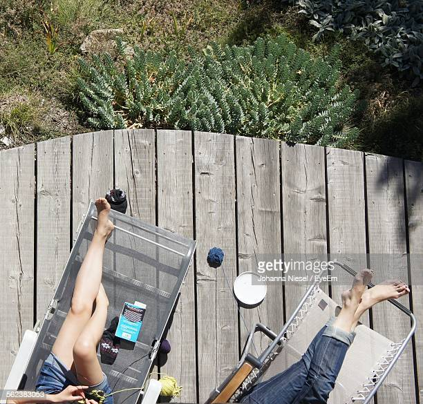 High Angle View Of Women Resting On Lounge Chairs In Yard