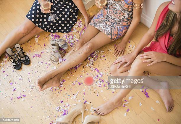 High angle view of women sitting on floor with confetti after party