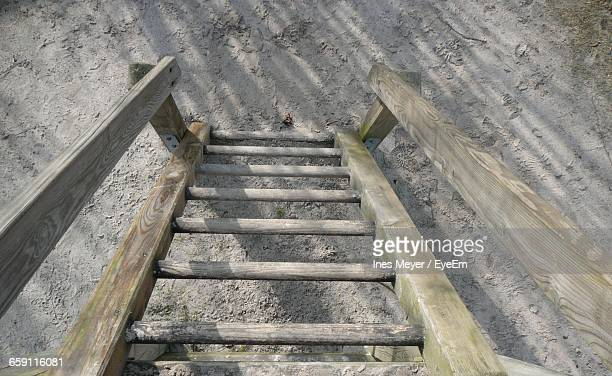 High Angle View Of Wooden Ladder On Sandy Field