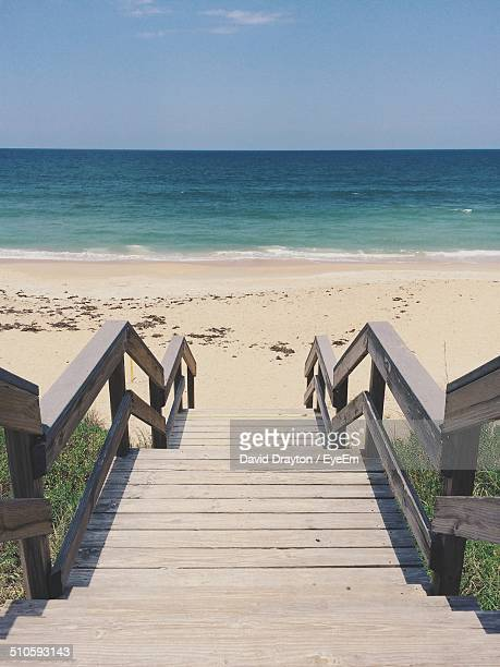 High angle view of wooden staircase leading towards beach