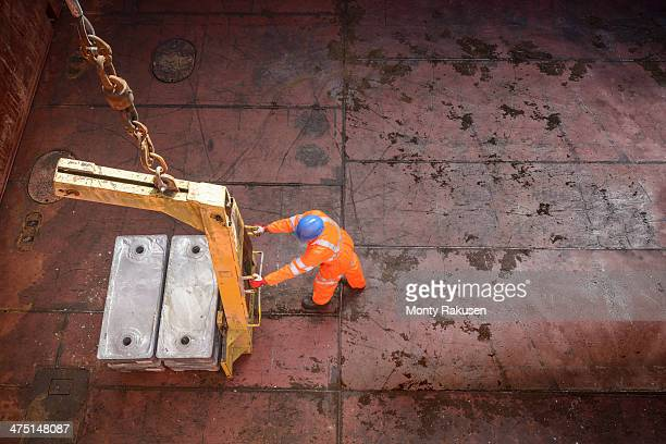 High angle view of worker unloading metal alloy ingots from ship's hold