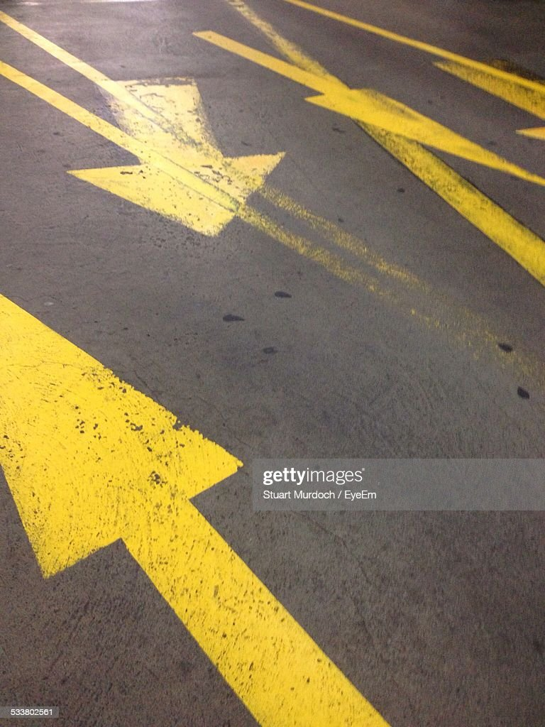 High Angle View Of Yellow Arrow Signs On Road
