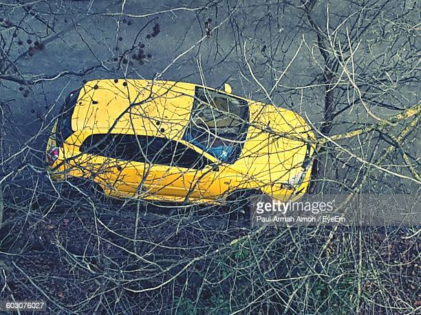 High Angle View Of Yellow Car On Road Seen Through Bare Tree Branches