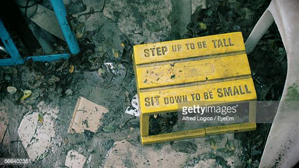 High Angle View Of Yellow Stool With Text