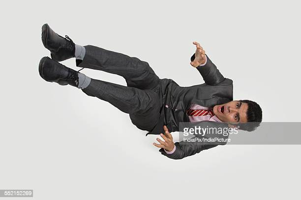 High angle view of young businessman falling against white background