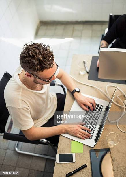 High angle view of young businessman using laptop in creative office