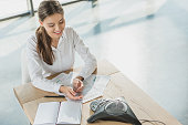 high angle view of young happy businesswoman doing paperwork and talking by conference phone on table at office