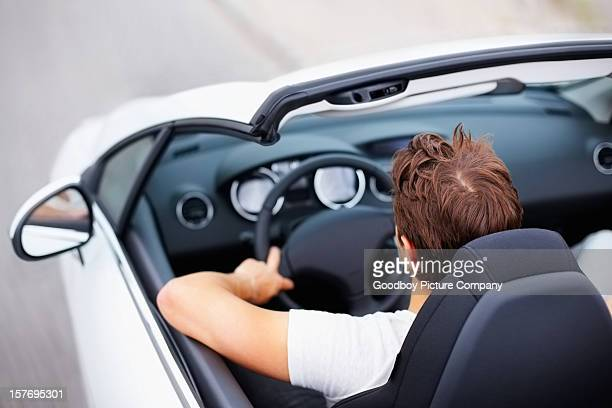 High angle view of young male driving convertible in speed