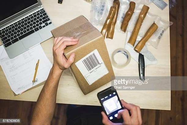 High angle view of young mans hands using smartphone to scan delivery label on package