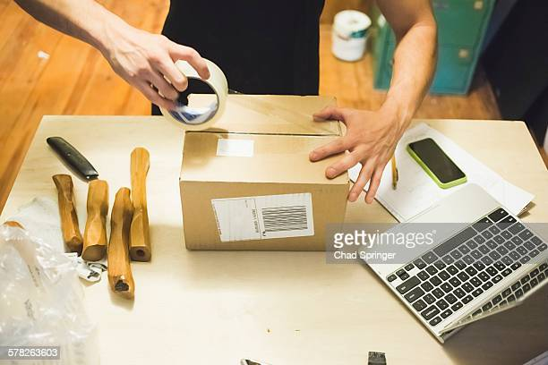 High angle view of young mans hands using sticking tape to prepare package for delivery