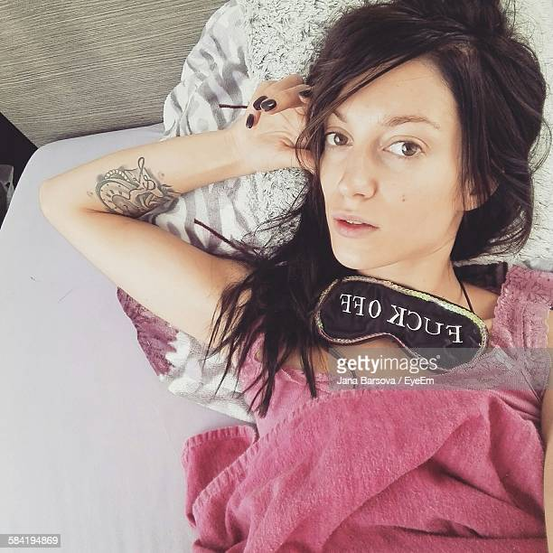 High Angle View Of Young Woman Relaxing On Bed At Home