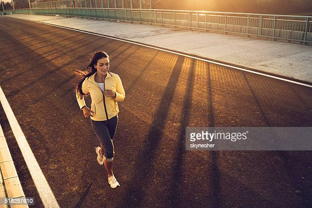 High angle view of young woman running at sunset.