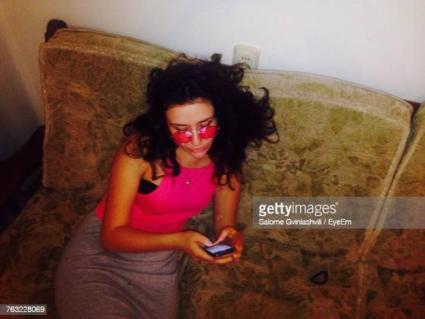 High Angle View Of Young Woman Using Phone On Sofa
