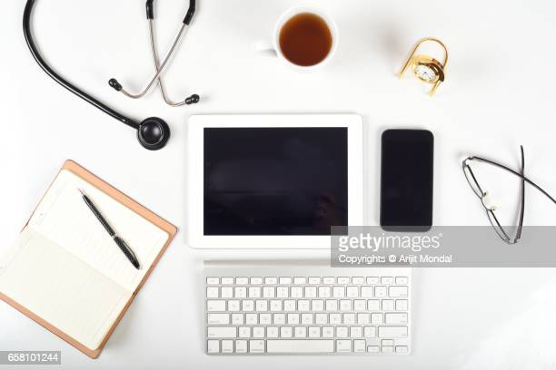 High Angle View Office Desk Of Modern Medical Clinic with computer Keyboard, Tablet, Smartphone With Blank Screen