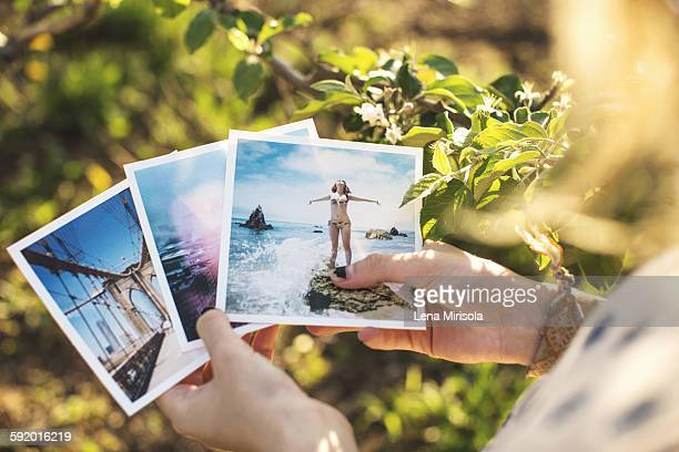 High angle view over shoulder of young woman holding photographs
