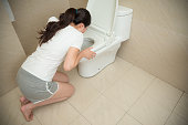 high angle view photo of sweet beautiful woman kneeling down in front of toilet vomiting on bathroom at home during pregnancy time.
