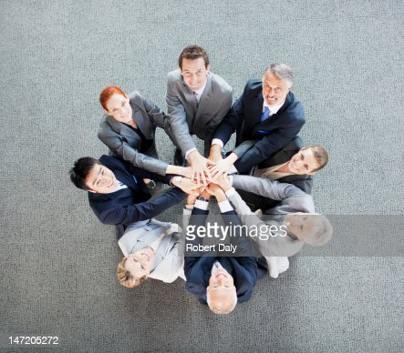 High angle view portrait of business people joining hands in circle : Stock Photo