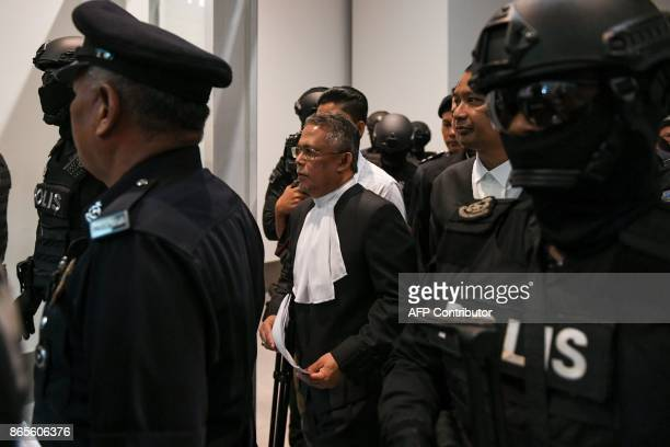 High Court judge Azmi Ariffin is escorted by police personnel at the lowcost carrier Kuala Lumpur International Airport 2 during a visit to the scene...