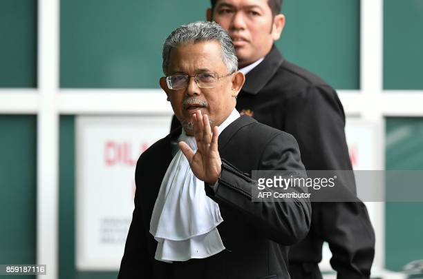 High Court judge Azmi Ariffin waves as he arrives at the Malaysian Chemistry Department in Petaling Jaya outside Kuala Lumpur on October 9 as part of...