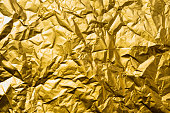 Detailed abstract crumpled light gold foil texture.